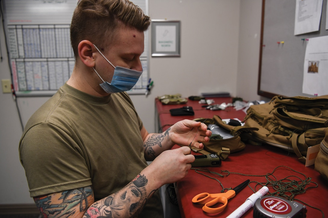 Staff Sgt. Brett Schindler, 445th Operations Support Squadron, aircrew flight equipment shop NCO in charge of helmets and chemical defense gear section, ties a lanyard to secure an escape and evasion kit inside an aircrew survival backpack at Wright-Patterson Air Force Base, Ohio Feb 12, 2021. The gear is used for aircrew survival during an emergency when they need to evacuate the aircraft.