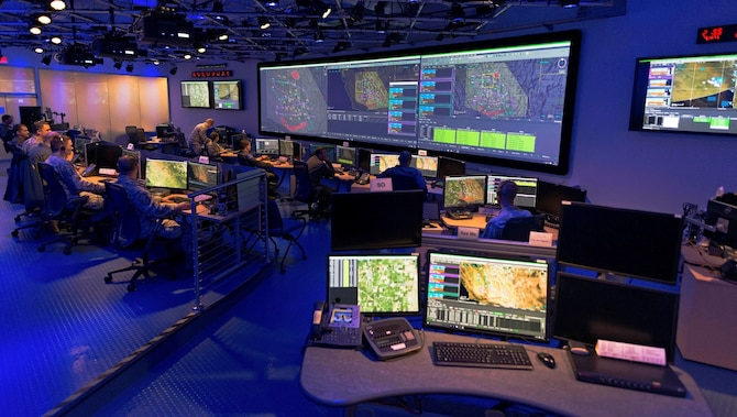 photo inside the Common Mission Control Center, Airmen working at computers