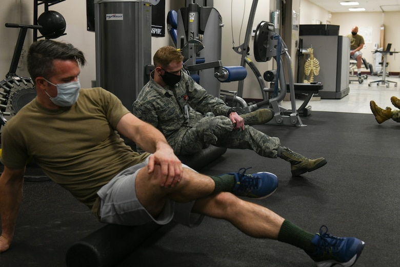 TSgt David Ferricher, 22nd Maintenance Squadron metals technician, and Senior Airman Heath Martin, 22nd Medical Operations Squadron physical therapy technician, uses a foam roller FOR their piriformis muscles Mar. 3, 2021, at McConnell Air Force Base, Kansas. Over the course of 30-45 minutes, participants in the class had the opportunity to execute and learn 12 foam rolling techniques. (U.S. Air Force photo by Senior Airman Nilsa Garcia)