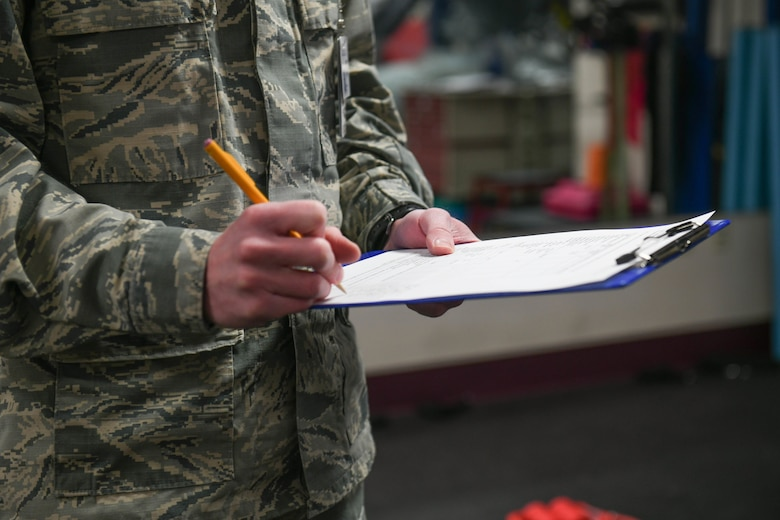 Senior Airman Heath Martin, 22nd Medical Operations Squadron physical therapy technician, records data Mar. 3, 2021, at McConnell Air Force Base, Kansas. The sheet provides an overall assessment of the patient's session that can be referred to by physical therapy technicians when an Airmen comes in for future classes. (U.S. Air Force photo by Senior Airman Nilsa Garcia)