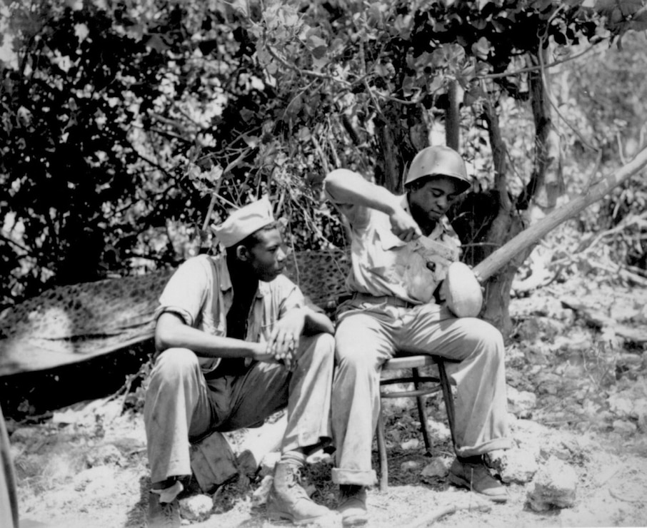 Marine Sgt. F. Smit and Cpl. S. Brown open a coconut to get a cool drink on Saipan, June 1944.