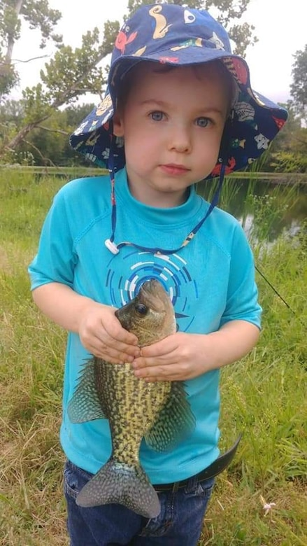 Anthony Gauna III holds a fish he caught by a lake.