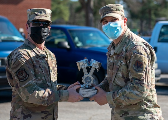 Lt. Col. Robert Fekete, left, 4th Logistics Readiness Squadron commander, presents Senior Airman Aaron Smith, right, 4th Civil Engineer Squadron pavement and equipment technician, with a trophy during a Vehicle Inspection Roll-By competition at Seymour Johnson Air Force Base, North Carolina, March 8, 2021.