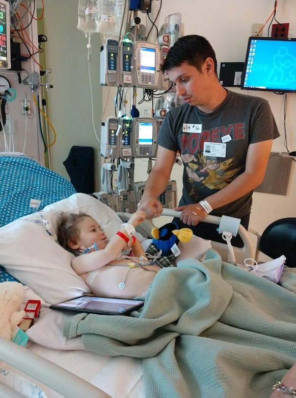 Senior Airman Anthony Gauna Jr. fist bumps with his son Anthony Gauna III in a hospital bed.