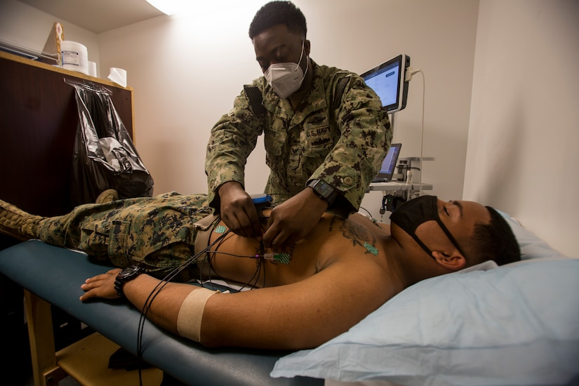 A sailor conducts a health assessment on a Marine attached to medical equipment.