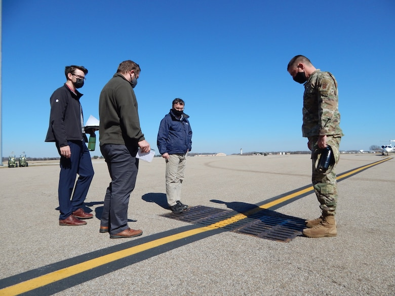 Lt. Col. Paul Fredin, commander of the 375th Civil Engineer Squadron, and 375th CES engineer Kenneth Cavanaugh (middle) talk with graduate students Kyle Collier and Cam Loyet (left to right) about water drainage on the flightline.  The students are taking the Innovating for Defense course at Washington University. They are working with Scott's Elevate innovation team on identifying solutions to prevent future flooding of Hangar 3, which is used to house and maintain C-21 aircraft. (Photo by Christi Spargur)