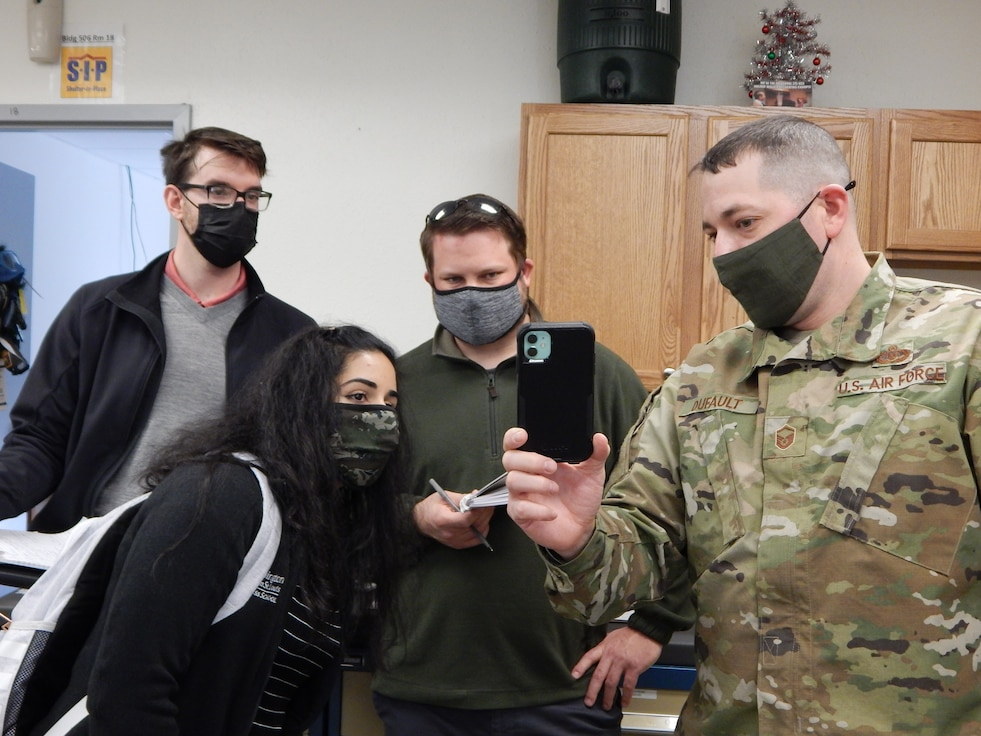 Master Sgt. Joseph Dufault, superintendent, Aircrew Flight Equipment, 375th Operations Support Squadron shows a video on his phone of the August 12, 2020, flooding of the AFE office to graduate students (left to right) Kyle Collier, Astha Bhatnagar, and Cam Loyet. The students are helping Scott's Elevate innovation team to find potential solutions to prevent future flooding. (Photo by Christine Spargur)