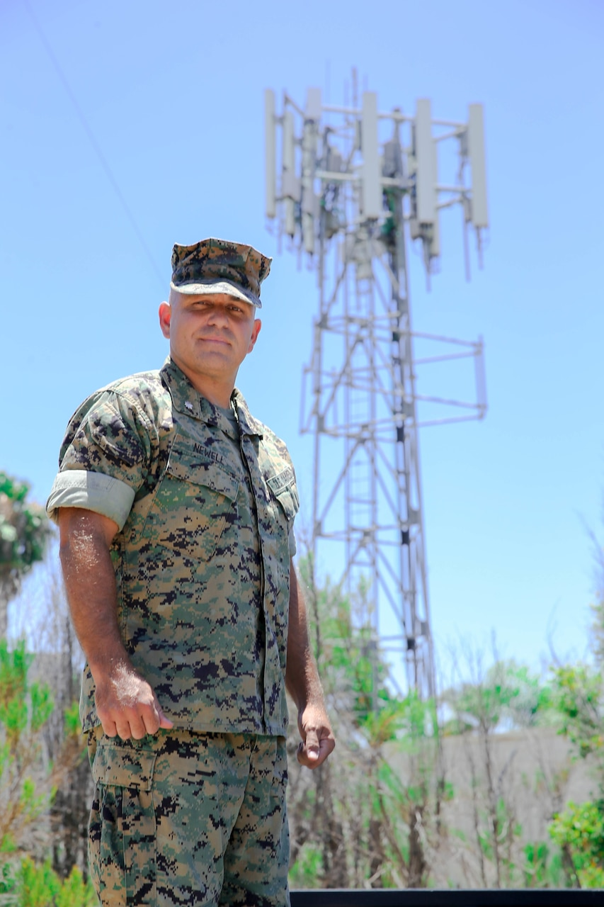 A Marine stands in front of a cell tower.