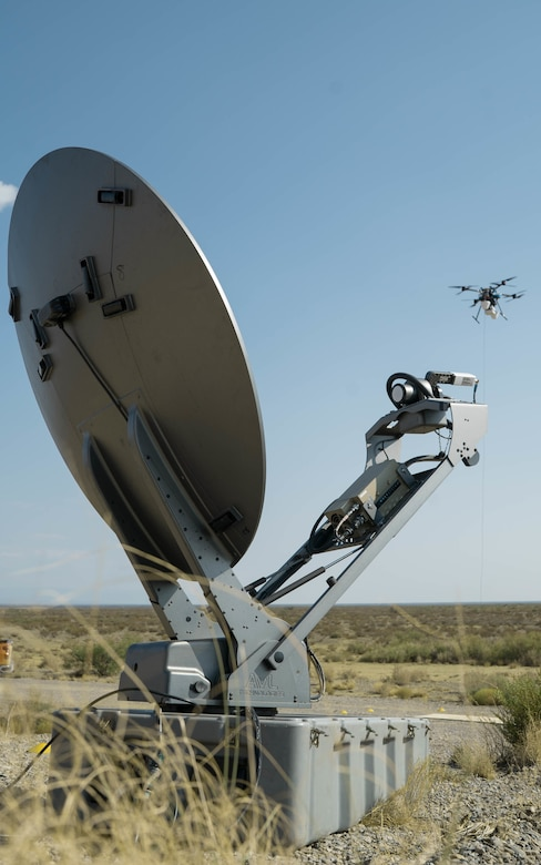 A drone flies past a satellite dish.