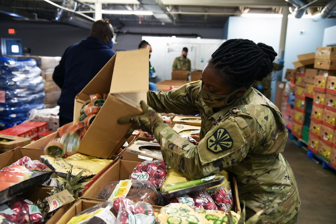 A soldier wearing a face mask and gloves tilts a box of food so that the contents fill into another box of food, as many boxes of food sit on a table.