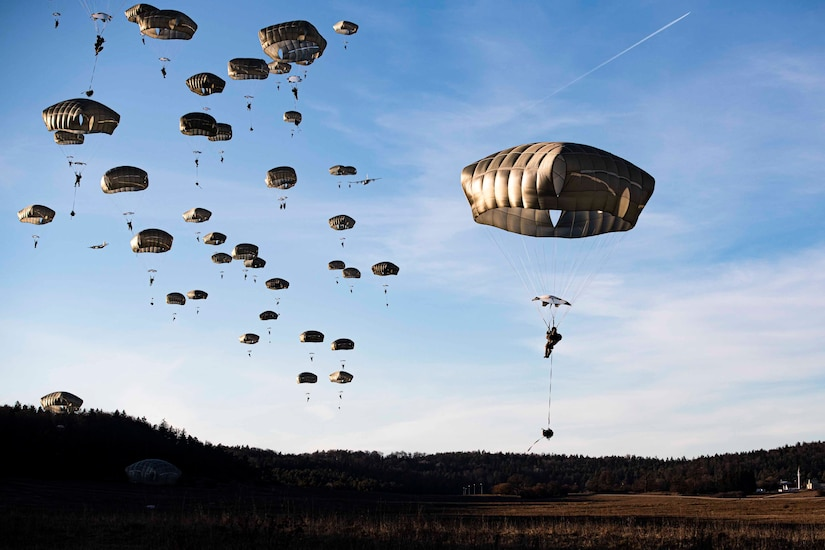 Soldiers wearing parachutes descend in the sky.