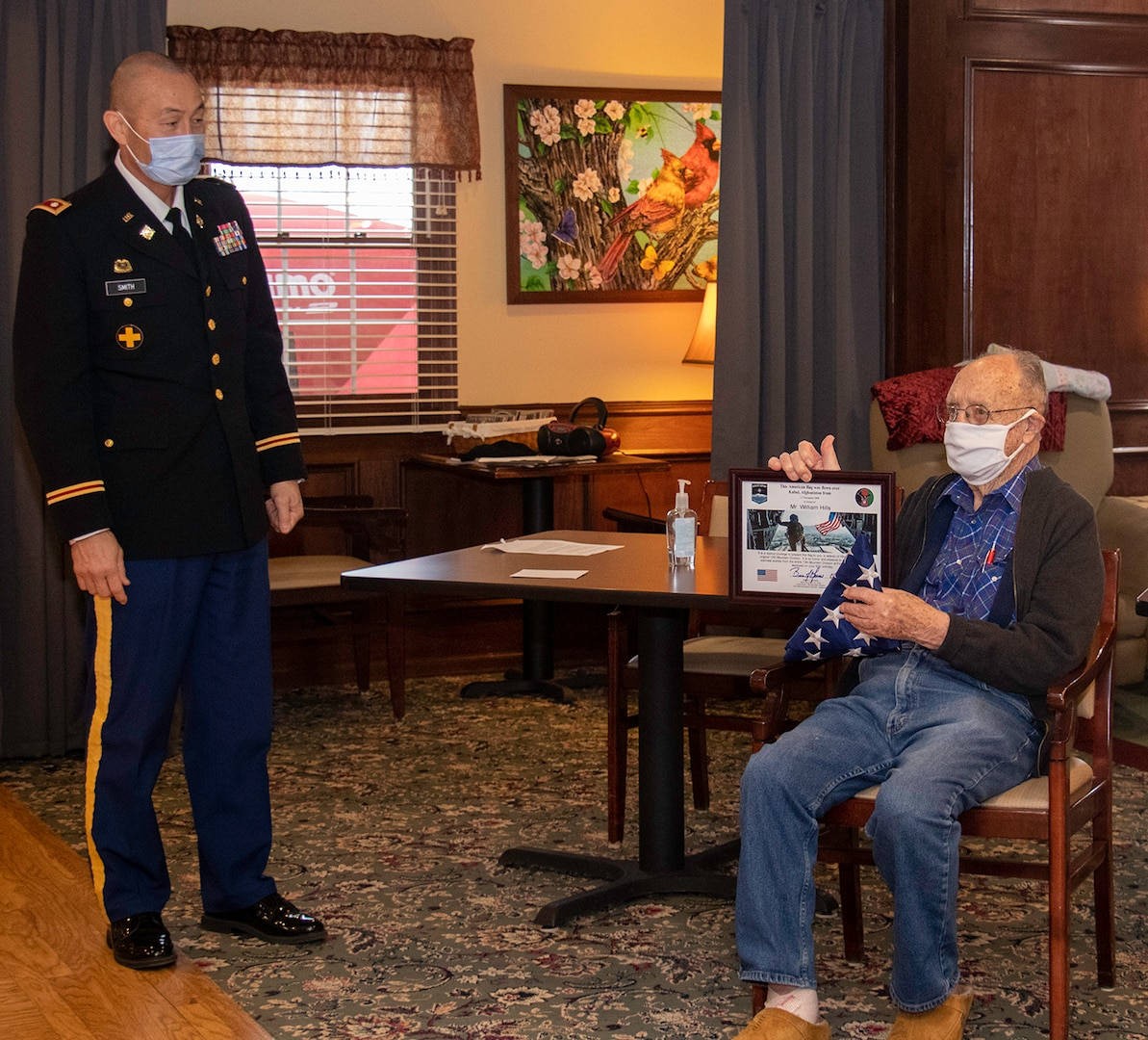 William Hills of Freeport, Illinois, shows off the U.S. flag and certificate presented by Lt. Col. Eric Smith of Springfield, Illinois, in honor of Hills' 97th birthday Jan. 29.