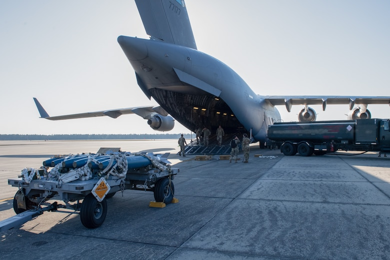 A photo of Airmen preparing to load a munitions trailer onto an aircraft