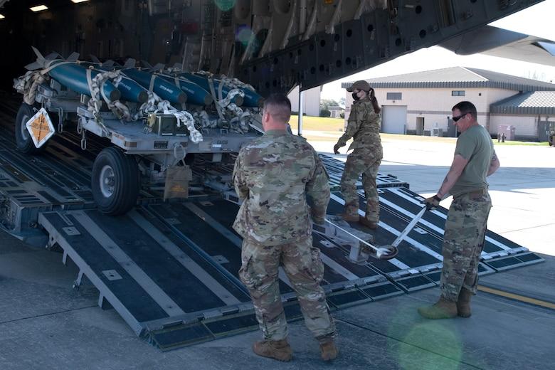 A photo of Airmen loading a munitions trailer onto an aircraft