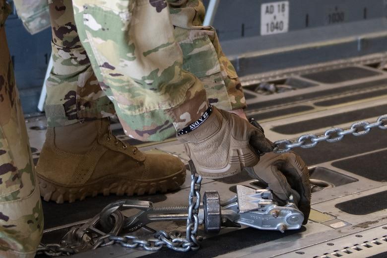 A photo of an Airman securing a munitions trailer onto an aircraft