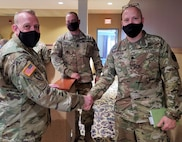 Two men in masks and uniform shake hands