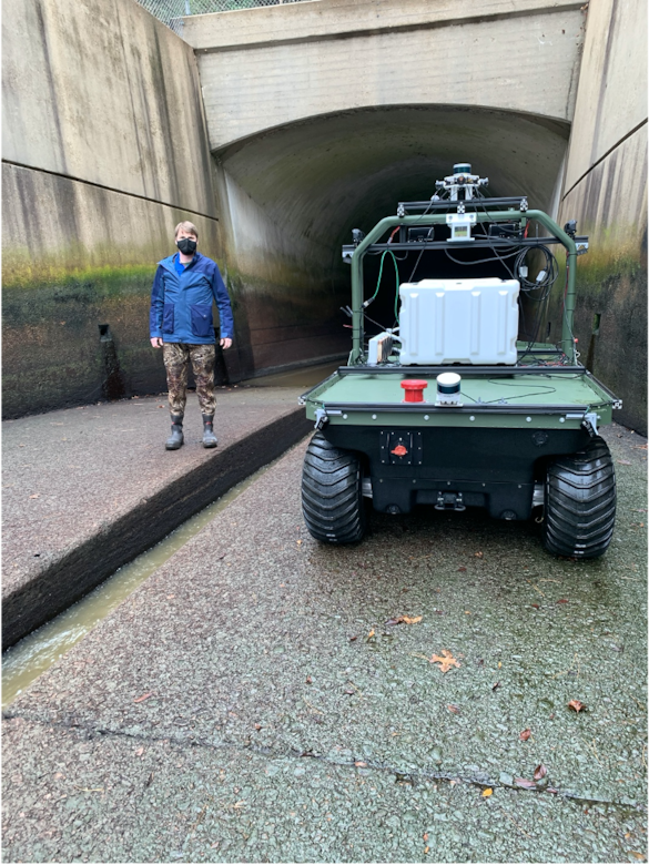 Principal Investigator Dr. Anton Netchaev stands near a robotic system known as the Dambot near the entrance of the outlet works at Blue Mountain Dam, Arkansas, in October 2020. Dambot takes the human element out of a dangerous but necessary U.S. Army Corps of Engineers (USACE) maintenance task. The cutting-edge technology has been successfully tested and stands poised to change the course of closure gate assessments, while also safeguarding USACE team members. (U.S. Army Corps of Engineers photo)