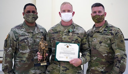 Chief Warrant Officer 2 Thomas Downer (center) receives and Army Commendation Medal from Brig. Gen. Kevin F. Meisler (right), commanding general of  the 4th Sustainment Command (Expeditionary), and 1st Sgt. Jorge Pimentel (left), 4th ESC Headquarter Company First Sergeant.