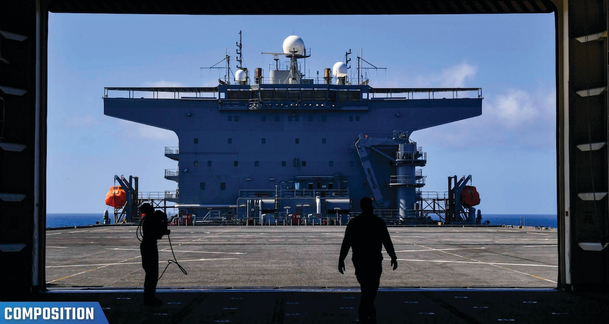 """Photo of two silhouettes of sailors performing maintenance outside the ship hangar bay of the Expeditionary Sea Base USS Hershel """"Woody"""" Williams (ESB 4)"""