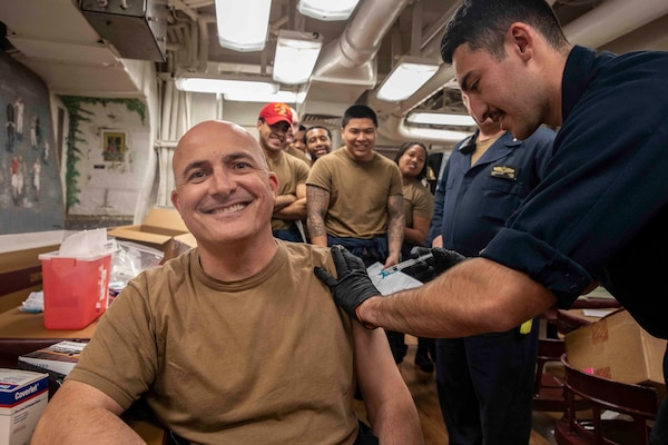 210220-N-BM428-0070 SOUDA BAY, Greece (Feb. 20, 2021) Cmdr. Thomas Ralston, commanding officer of the Arleigh Burke-class guided-missile destroyer USS Porter (DDG 78), receives the COVID-19 vaccine from Hospital Corpsman Kevin Gonzalez in Souda Bay, Greece, Feb, 20, 2021. Porter, forward deployed to Rota, Spain, is on its ninth patrol in the U.S. Sixth Fleet area of operations in support of U.S. national interests and security in Europe and Africa. (U.S. Navy photo by Mass Communication Specialist 2nd Class Damon Grosvenor)