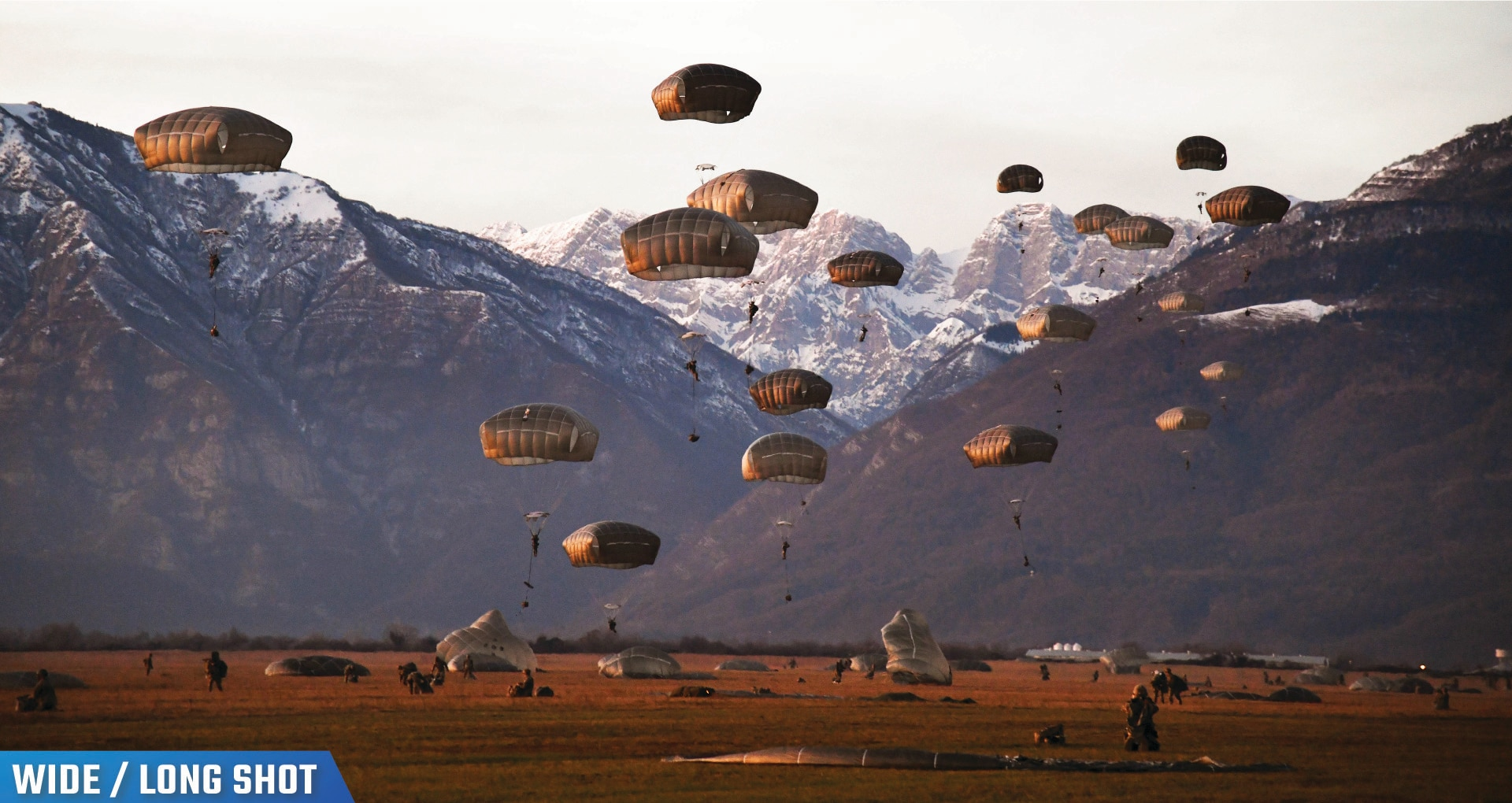 Soldiers freefall wearing parachutes near mountains