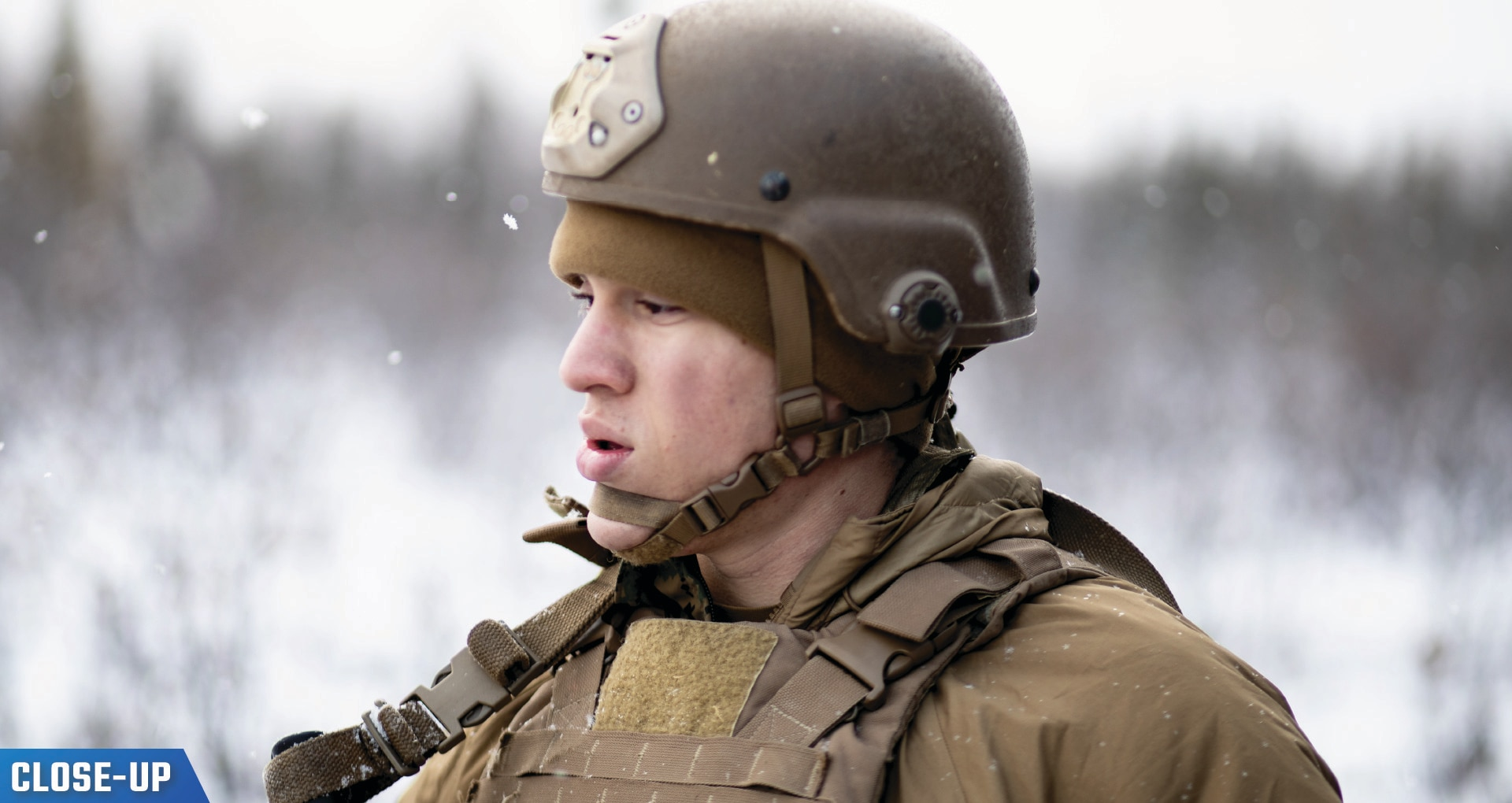 U.S. Marine Corps Lance Cpl. in gear standing in snow.