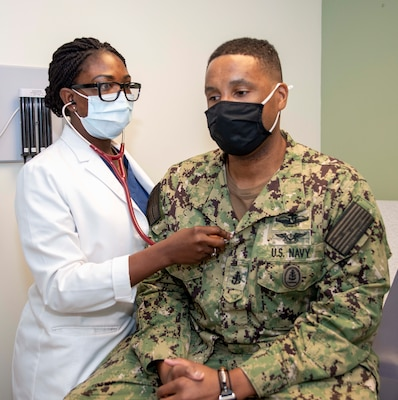 Lt. Abiola Babawale, an internal medicine intern at Naval Medical Center Portsmouth, uses a stethoscope on CMDCS Terrance Foote, the command senior chief of Virginia Military Institute, during a routine appointment.