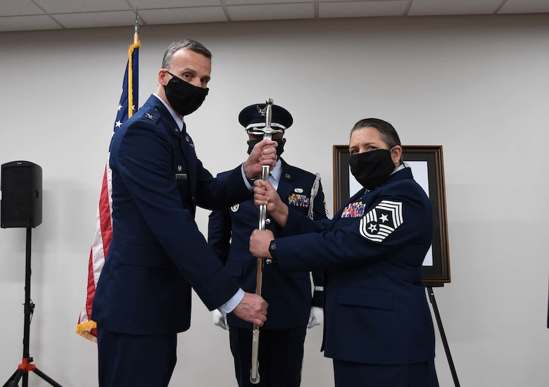 U.S. Air Force 145th Airlift Wing (AW) Command Chief Master Sgt. Susan A. Dietz ceremoniously hands off a sword as a symbol of turning over authority as the Command Chief of the 145th AW during a Change of Authority Ceremony held at the North Carolina Air National Guard Base, Charlotte Douglas International Airport, March 6, 2021. CMSgt Dietz, relinquishes authority of the 145th AW Command Chief position as CMSgt William R. Harper, Jr. accepts authority.