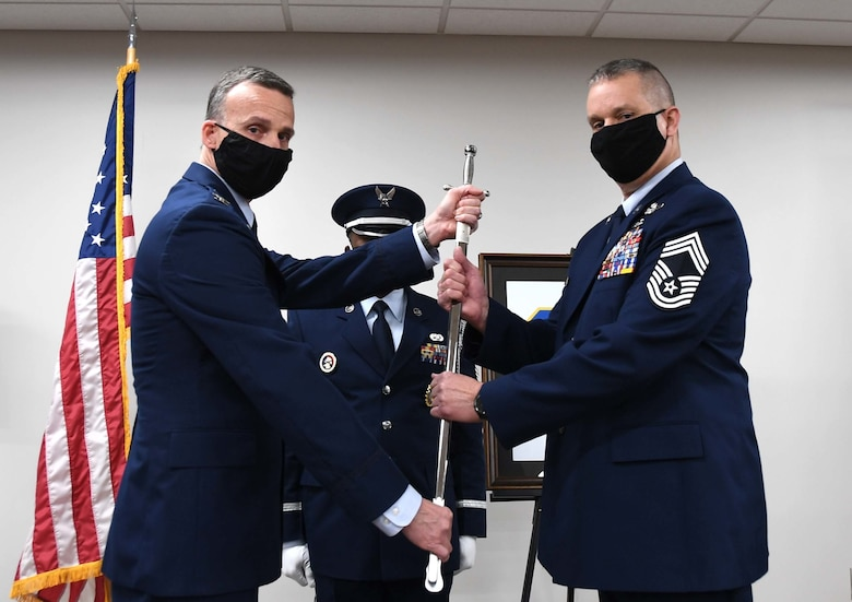 U.S. Air Force 145th Airlift Wing (AW) Command Chief Master Sgt. William R. Harper, Jr. ceremoniously accepts a sword as symbolism of taking over authority as the new Command Chief of the 145th AW during a Change of Authority Ceremony held at the North Carolina Air National Guard Base, Charlotte Douglas International Airport, March 6, 2021. CMSgt Susan A. Dietz, relinquishes authority of the 145th AW Command Chief position as CMSgt Harper, accepts authority.