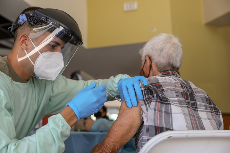 Sgt. Phillip Altuz of the Puerto Rico Army National Guard vaccinates a person at Aguadilla, Puerto Rico, March 4, 2021. The Puerto Rico National Guard assisted the Department of Health to vaccinate the elderly against COVID-19. (U.S. Army National Guard photo by Spc. Hassani Ribera)