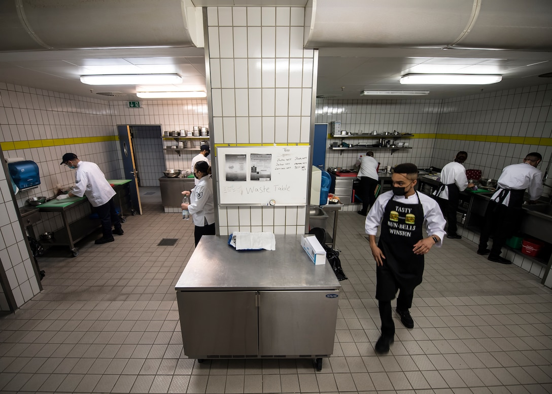 People prepare to cook in two side-by-side rooms. A man is quickly walking out of one of the rooms.