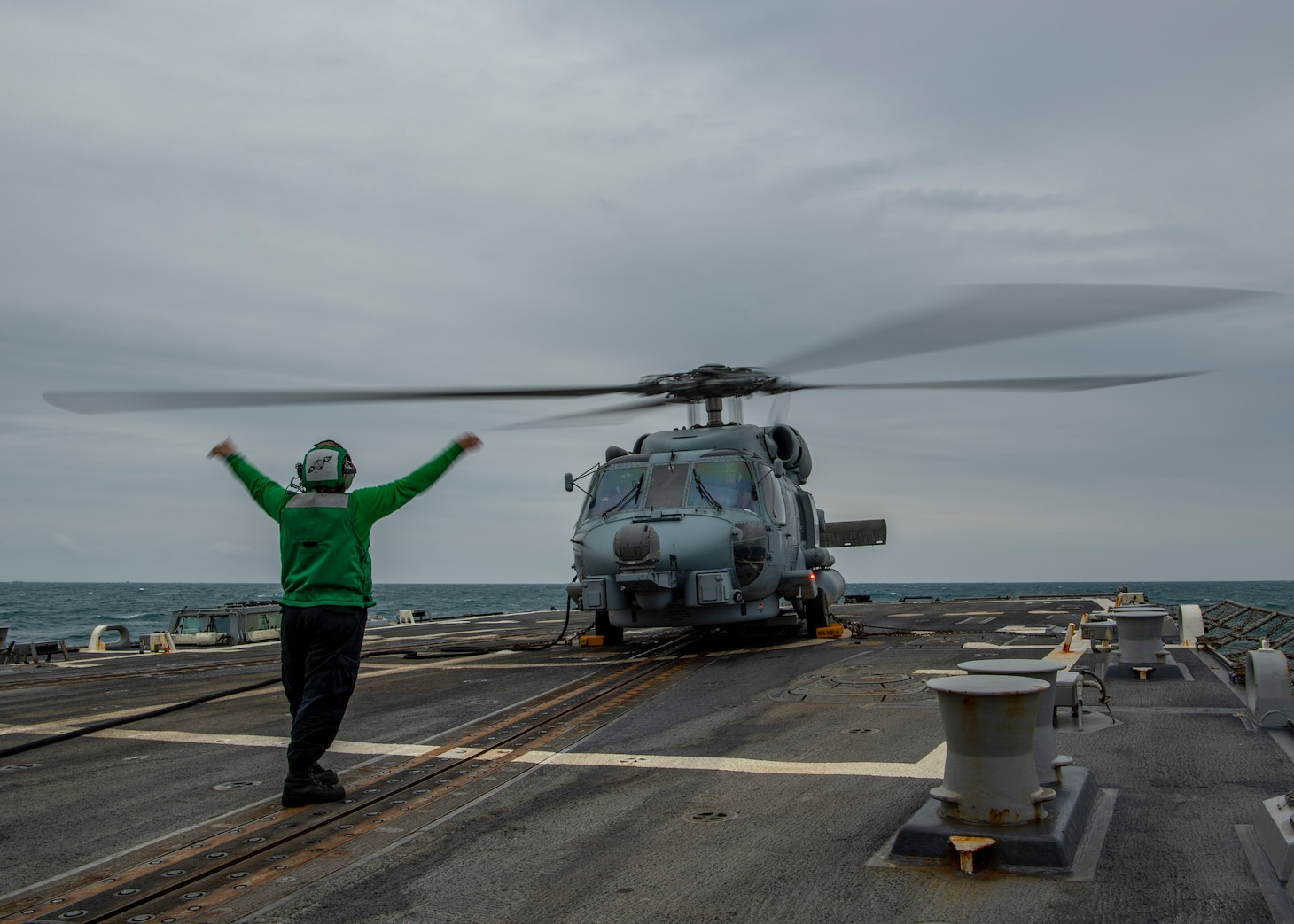 """210310-N-SS350-1022 EAST CHINA SEA (March 10, 2021) U.S. Navy Aviation Electrician's Mate 2nd Class Elizabeth Larson, from Porter, Texas, assigned to the """"Magicians"""" of Helicopter Maritime Strike Squadron (HSM) 35, signals to the pilots in an MH-60R Sea Hawk on the flight deck of the Arleigh Burke-class guided-missile destroyer USS John Finn (DDG 113) March 10, 2021. John Finn, part of the Theodore Roosevelt Carrier Strike Group, is on a scheduled deployment to the U.S. 7th Fleet area of operations. As the U.S. Navy's largest forward-deployed fleet, 7th Fleet routinely operates and interacts with 35 maritime nations while conducting missions to preserve and protect a free and open Indo-Pacific Region. (U.S. Navy photo by Mass Communication Specialist 3rd Class Jason Waite)"""