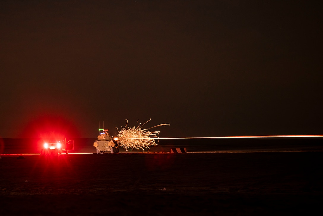 Sparks fly after Marines fire a weapon in the dark illuminated by red lights from a vehicle.
