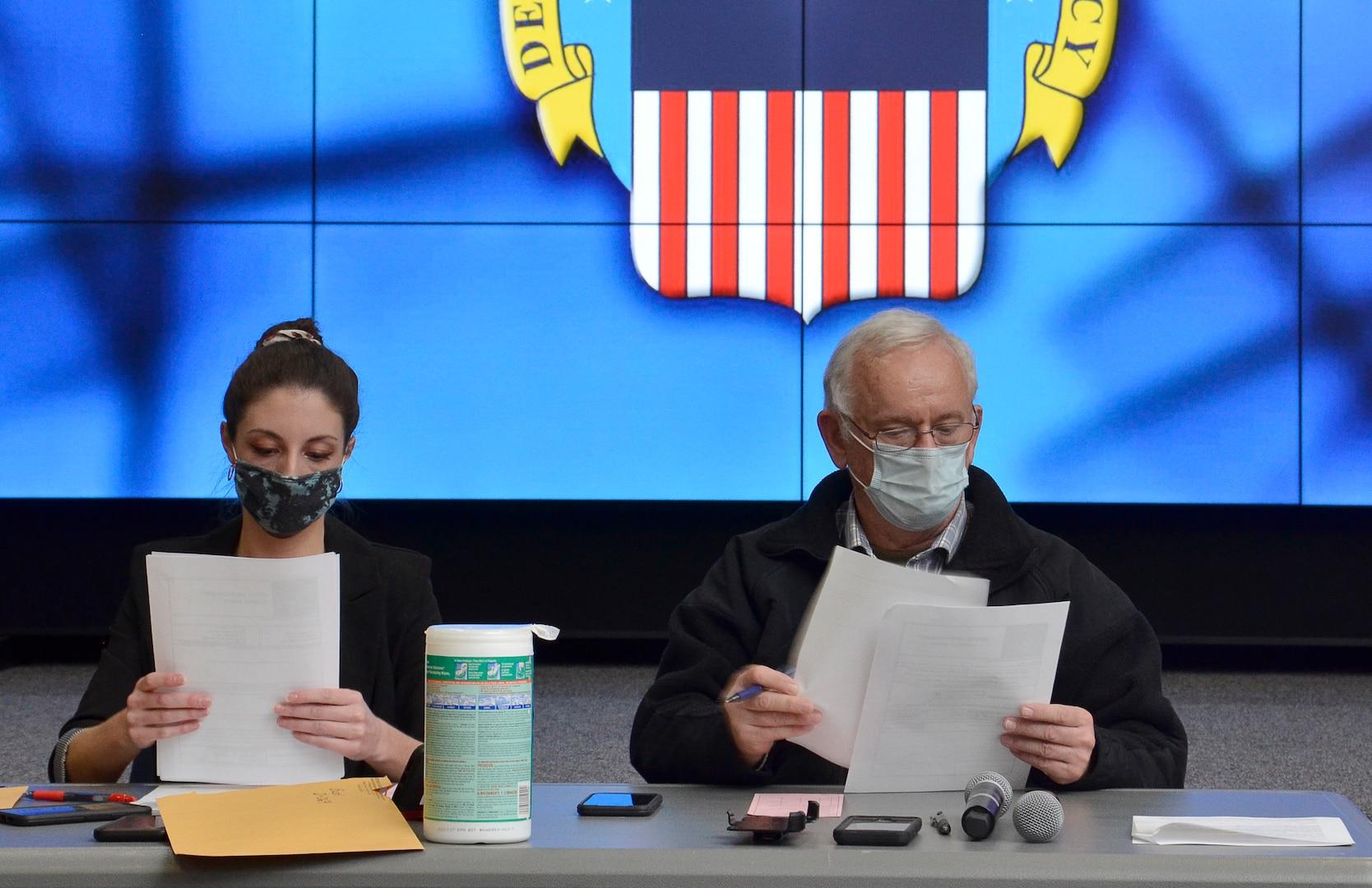 Two masked DLA employees open sealed bid envelopes.