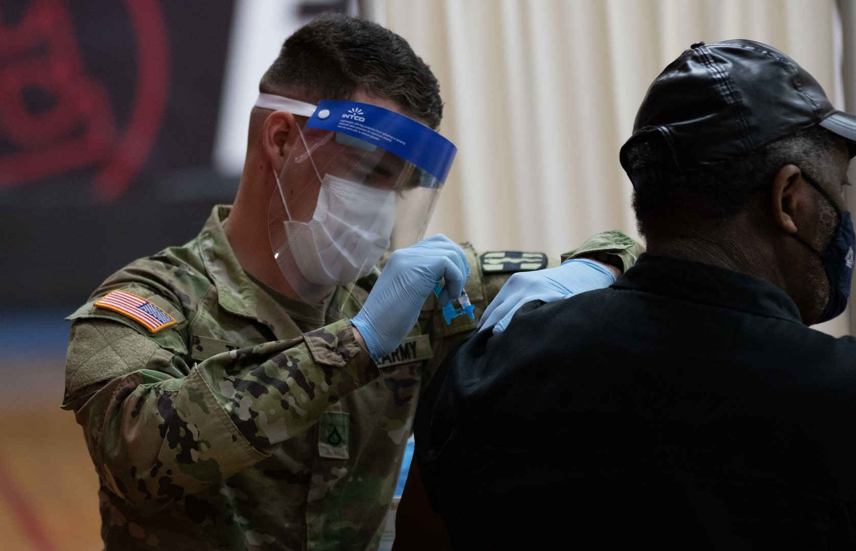 Service member administers vaccine to elderly man