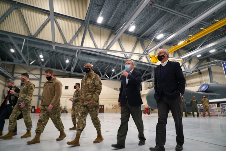 Col. Cameron Pringle, 319th Reconnaissance Wing commander, (third from left), Air Force Chief of Staff Gen. Charles Q. Brown, Jr., Sen. John Hoeven and Senator Kevin Cramer, depart an aircraft hangar at Grand Forks Air Force Base, N.D., Feb. 17, 2021. Brown received a brief from members of the 319th Aircraft Maintenance Squadron, who shared information regarding the critical role the RQ-4 Global Hawk plays in the Air Force's intelligence, surveillance and reconnaissance mission. (U.S. Air Force photo by Staff Sgt. Elora J. McCutcheon)