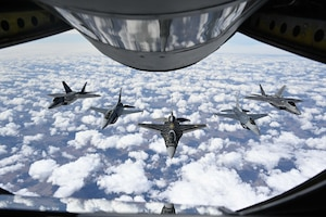 Pilots with the F-16 Viper and F-22 Raptor Demonstration Teams fly behind a KC-135 Stratotanker from the 465th Air Refueling Squadron assigned to Tinker Air Force Base, Oklahoma March 8, 2021. The F-16 team from Shaw Air Force Base, South Carolina, and the F-22 team from Joint Base Langley–Eustis, Virginia, are assigned to Air Combat Command and received fuel from the Okies during their flight back to their home stations after performing at an air show. (U.S. Air Force photo by Senior Airman Mary Begy)