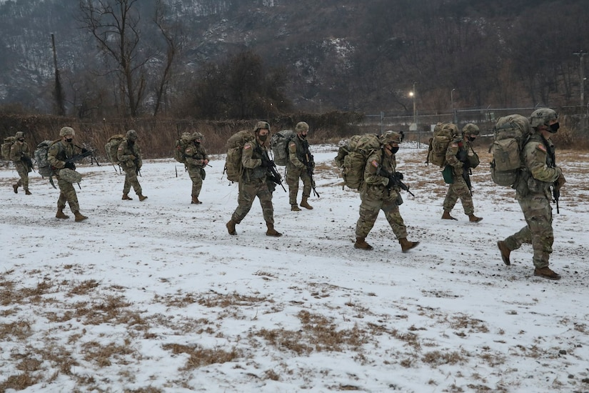 A group of soldiers march along a snow-covered trail.