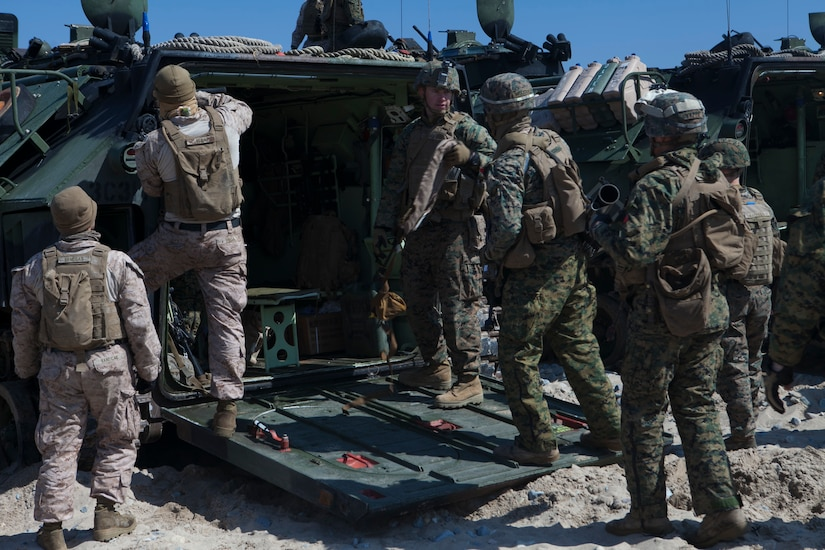 Service members gather around the rear opening of a combat vehicle.