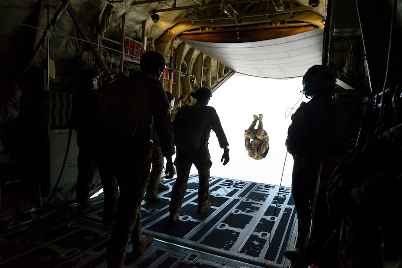 Several service members gather in the rear of an aircraft. Another has jumped out and appears to be suspended in the air.