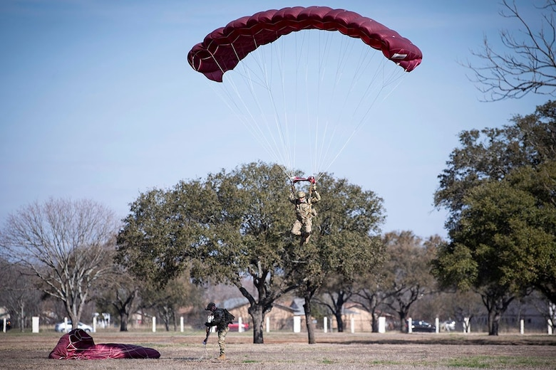A member of the Special Warfare Training Wing prepares to land after parachuting over Airmen's Heritage Park during a Medal of Honor plaque unveiling ceremony to honor Master Sgt. John Chapman at Joint Base San Antonio-Randolph March 4, 2021.