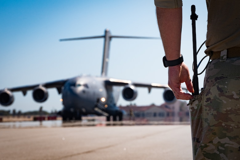 A photo of an Airman waiting for an Aircraft to taxi in