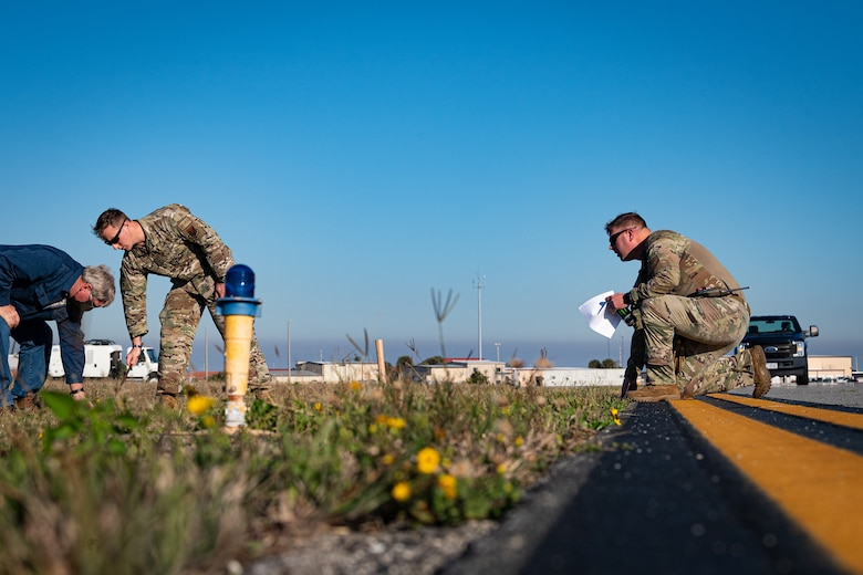 A photo of Airmen placing grounding rods on an airfield