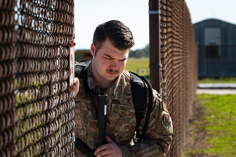 A photo of an Airman opening a gate