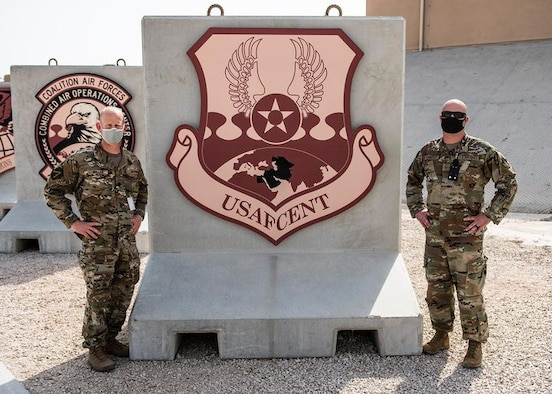U.S. Air Force Lt. Col. Jake Miller (left), U.S. Air Forces Central deputy chief of staff, and Master Sgt. Tyler Kermoade (right), 609th Expeditionary Air Communications Squadron plans and programs flight chief, pose for a photo outside the Combined Air Operations Center at Al UDeid Air Base, Qatar, March 10, 2021.