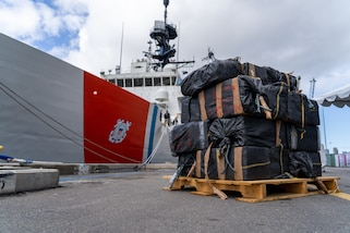 The crew of the Coast Guard Cutter Bertholf (WMSL-750) offloads approximately 7,500 pounds of seized cocaine and marijuana in San Diego, March 20, 2021.