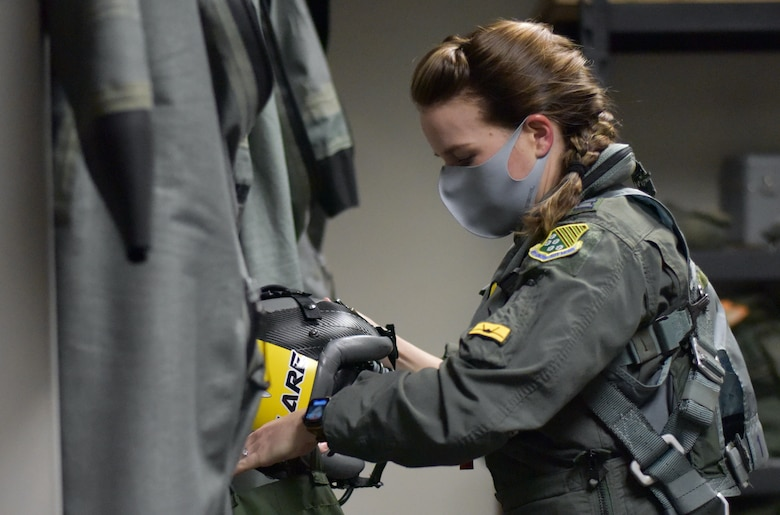 Pilot with pony tail putting on gear
