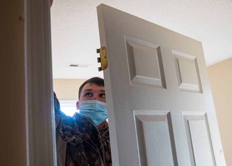 Photo of Airman putting together a door