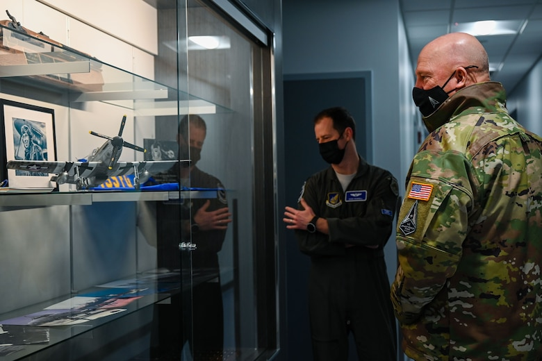 """U.S. Air Force Lt. Col. Ryan Worrell, the 355th Fighter Squadron director of operations, and U.S. Space Force Gen. John W. """"Jay"""" Raymond, Chief of Space Operations, look at a heritage display on Eielson Air Force Base, Alaska, March 10, 2021."""