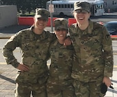 Three women in military uniform stand together